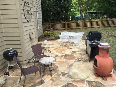 Stone patio in back with a charcoal grill and gas grill and plenty of seating