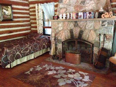 Twin bed in LOG CABIN with fire place sitting area and KING bed on other side