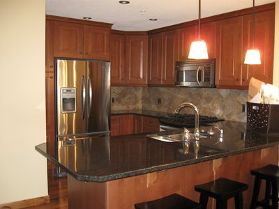 Open gourmet kitchen with granite countertops and seating for 3