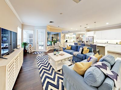 """Living Room - The open-concept living room boasts a cool coastal style and a 55"""" TV."""