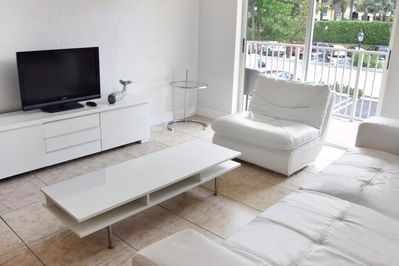 Nicely appointed living room with seating area and flat screen TV