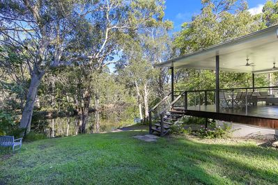 The house revolves around a very large deck in the trees above the river.