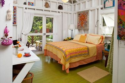 The romantic bedroom opens onto the oversized covered porch.