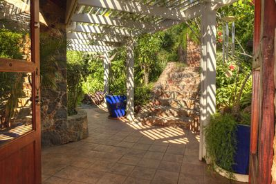 Stone steps descend through lush gardens to Andante's Arched Entrance Door