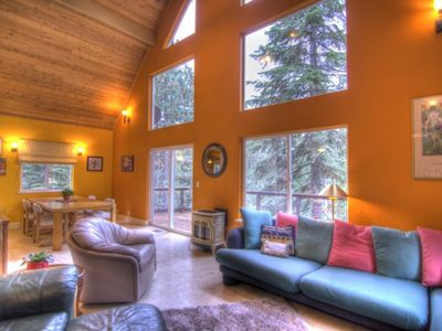 Large south-facing windows in great room with large dining table, Gas Log Stove.