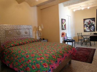 Studio apartment with queen bed, eating area, kitchen and bath.