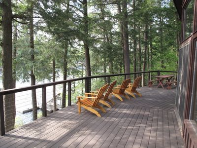 Huge deck overlooking the lake with Adirondack chairs and picnic table