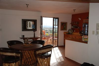 Dining area with french doors opening with views of town and valley.