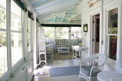 Spacious porch with antique wicker . . . perfect for reading and people watching