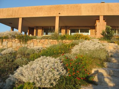 Photo for Charming beach front villa, private garden, sea view with breath-taking sunsets either from inside/outside the house