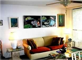 Living room with futon couch and reef fish pictures.