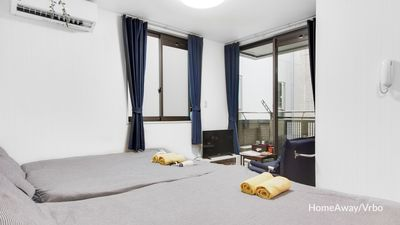 Overview of the room with two double beds, air conditioner and television