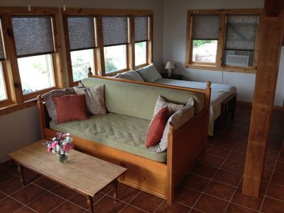 Living area daybed with trundle underneath and queen bed behind.
