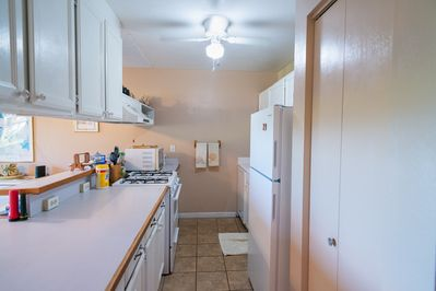 Kitchen with gas stove, range, dishwasher, fridge and microwave.