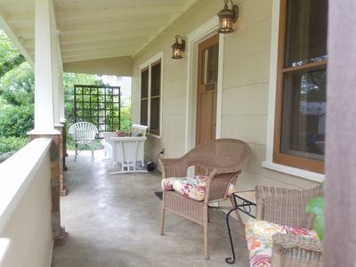 Welcoming front porch with classic glider.   Cool shade and street view.