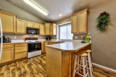 Kitchen with stove, microwave, pantry, dishwasher, disposal and refrigerator