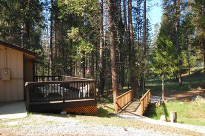View of back deck and foot bridge over seasonal stream opening up into the natural wedding site