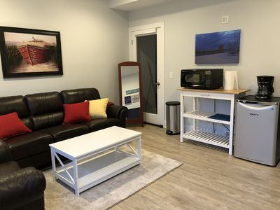 Sitting area with TV, microwave, coffee pot and mini refrigerator.