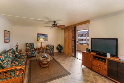 Living room rattan couch and 2 armchairs facing TV