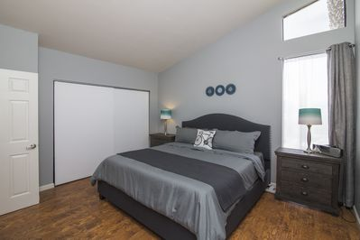Spacious master bedroom has a large closet and laminate wood flooring