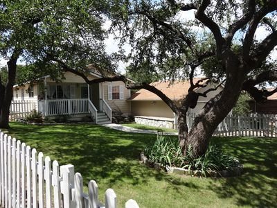Fenced in front yard with shade from mature oak trees