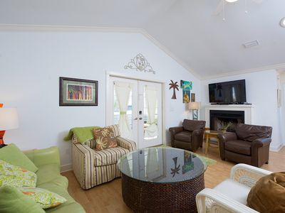 The living area has a large, wall-mounted flat screen TV & door to screened deck