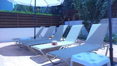 Sunbeds and umbrellas in back poolside area