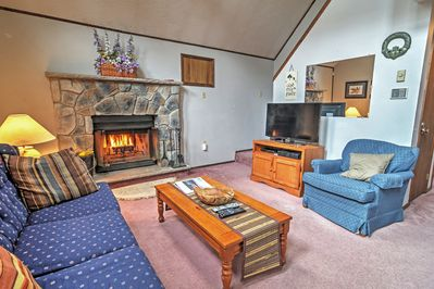 This lovely vacation rental features a stone fireplace and comfy seating.