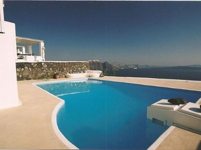 The pool and view of the caldera, the volcano and the Aegean sea