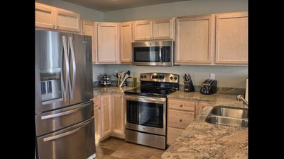 Fully stocked kitchen - complete with granite countertops & stainless appliances