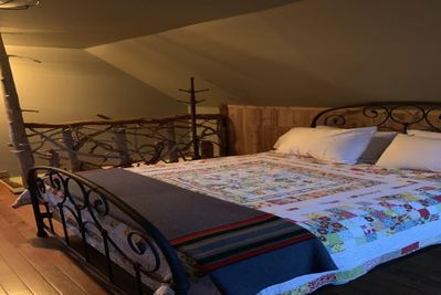 The sleeping loft features a queen bed and two built in twins with great details