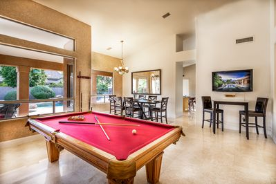 Bright and open game room with pool table and TV.