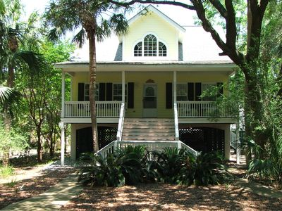 Front of house with porch swing and three rocking chairs.