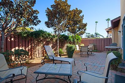Large private patio with sitting area, table, and gas grill