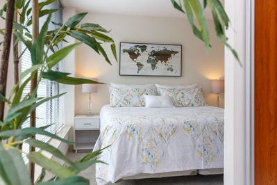 King bed with cozy linens in master bedroom with ensuite bathroom.