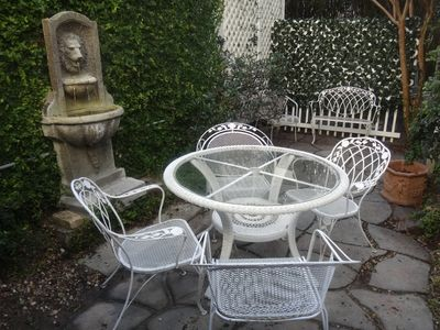 There is a private backyard patio w/ an outdoor table, chairs, bench & fountain.