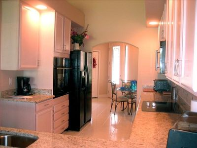 Large kitchen with granite countertops.