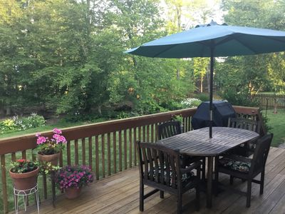 Deck with grill looks out onto lawn and small wooded area