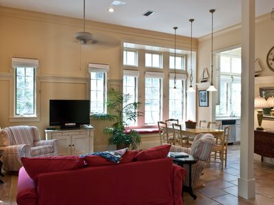 The high ceilings and abundant windows fill the great room with light. This room also has tile floors, recessed lights, ceiling fan, and flatscreen TV.