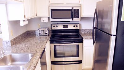 Bright kitchen with new granite and stainless steel appliances.