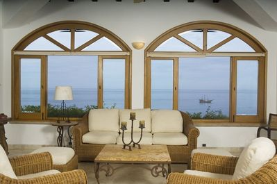 Living room with arched windows and sliding glass doors on both sides to decks.