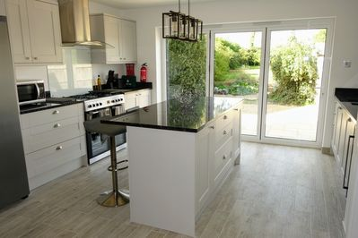 Kitchen with granite worktops, range cooker, bifold doors to garden