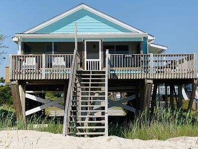 View of ocean side of cottage. Outdoor deck w/picnic table, chairs, screen room
