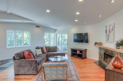 """The living area features high ceilings, decorative fireplace, 55"""" TV with Cable"""