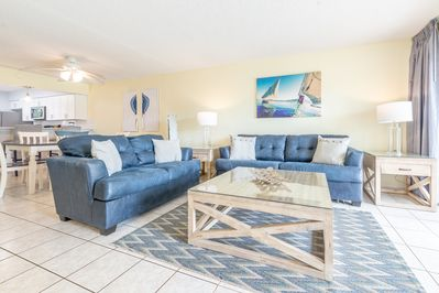 """Living room with 55"""" TV & queen sleeper. Walk out to your private patio & yard!"""