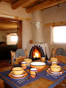 Great room gas log kiva fireplace, festive dinner ware showing one of two great room dining areas