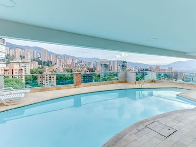 Photo for Modern city-view studio with shared pool and rooftop deck