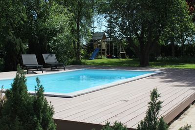 Pool with garden view and play area