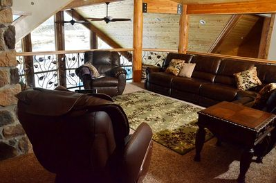 Comfortabe loft with leather reclining couches, chairs, and massage chair.