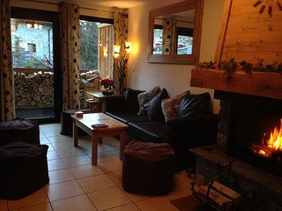lounge with flat screen tv, dvd player, blue tooth speaker and open log fire